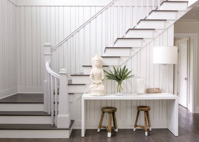 This simple and bright Beach-style foyer has elegant white wooden finish with shiplap patterns. This blends with the white console table beside the white staircase adorned with a Buddha statuette and a table lamp all with light hues that contrast the dark hardwood flooring.