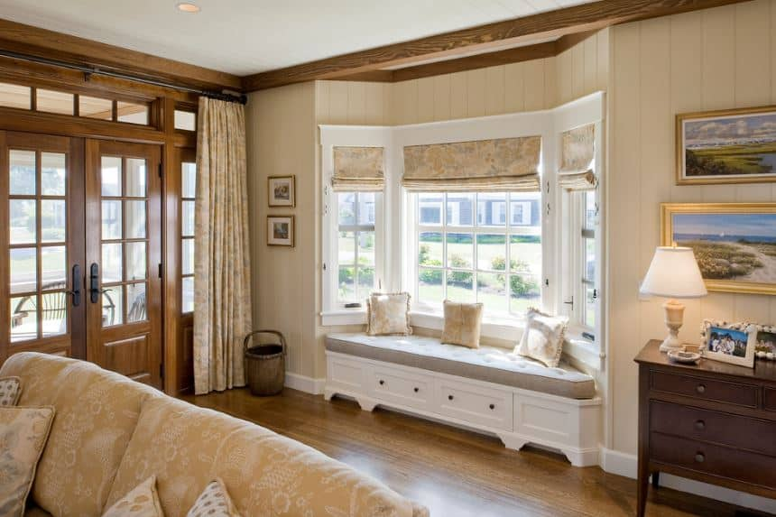 Upon entry of the wooden double doors of this foyer, you are welcomed with a comfortable seating area by the window nook within the beige walls that is complemented by the hardwood flooring and the dresser on the side.
