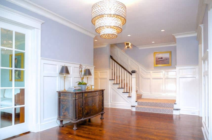 This simple foyer has a dark hardwood flooring that blends with the low cabinet against the white wainscoting of the light gray walls illuminated by the brilliant three-tier lighting with a brass golden hue hanging from the white ceiling.