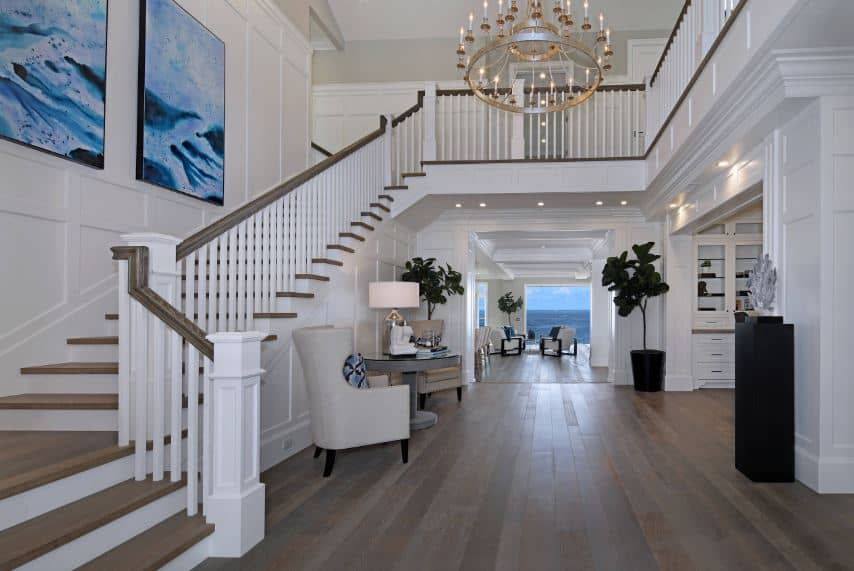 This large foyer has a high ceiling further than the second level of the house. This is adorned with a large chandelier hanging over the dark hardwood flooring that contrasts the white walls that is accented with large blue paintings by the stairs.