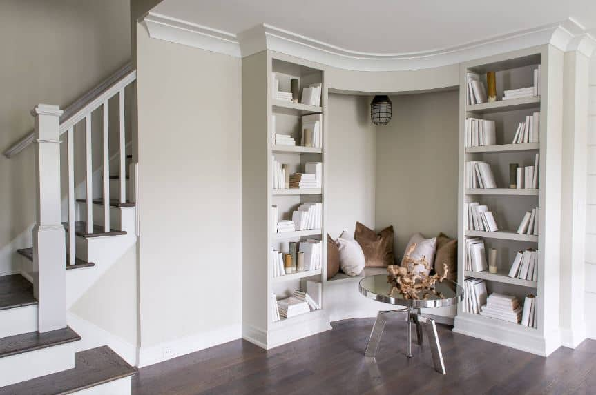 This Beach-style foyer offers its guests a comfortable sitting area in a nook beneath the stairs. This is flanked by bookshelves and paired with a modern circular coffee table that complements the dark hardwood flooring.