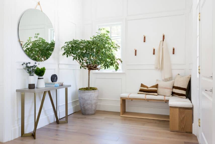 The white and bright wooden walls of this Beach-style foyer are warmed by the L-shaped wooden bench on the corner by the door along with a potted plant that brings a dash of green color to the walls brightened by the window.
