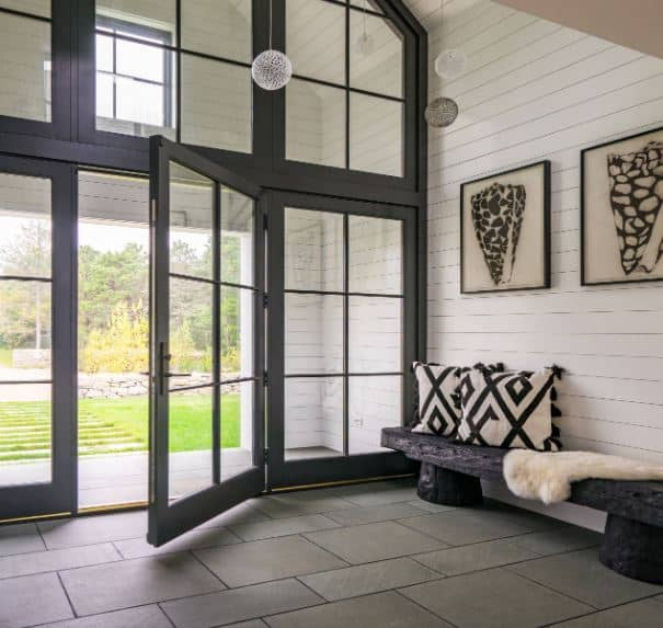 The entryway of this Beach-style foyer has a large glass wall from the gray stone floor to the high white shiplap cathedral ceiling. This brings in a lot of natural lighting as well as a great view of the lush landscaping outside.