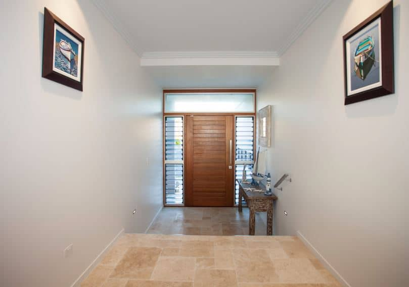 This simple hallway-like foyer has beige marble flooring that complements the wooden main door with glass side lights and transom window. This pairs well with the wooden console table on the side that bears decors with a seaside theme.