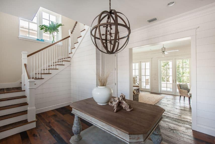 Upon entry of this Beach-style foyer, guests are welcomed by a gray farmhouse-style wooden table in the middle of the hardwood flooring. This is topped with decors and a large spherical pendant light with a dark brown hue contrasting the white walls.