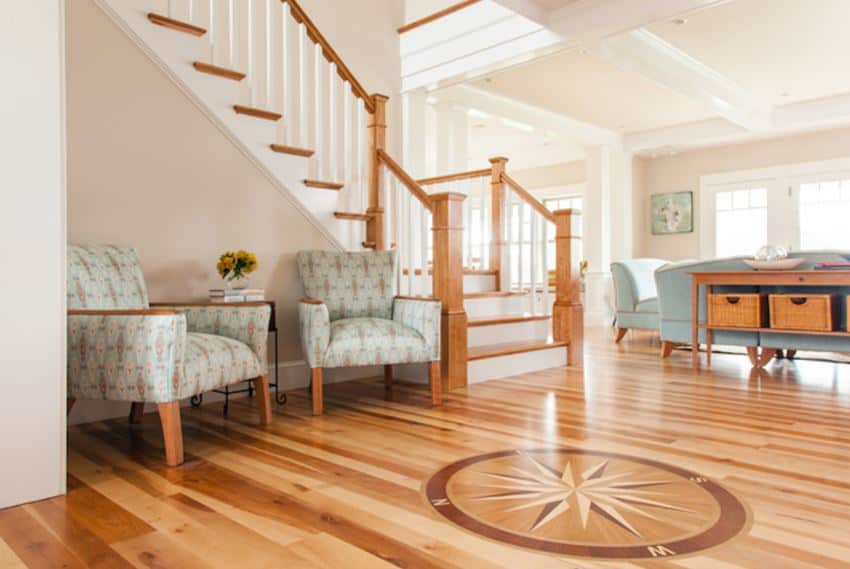 This Beach-style foyer's hardwood flooring is adorned with a seafaring compass in the middle of the foyer under the beige coffered ceiling. There is a comfortable sitting area with two cushioned green armchairs on the side for the guests by the stairs.
