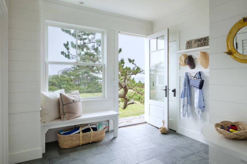 The simple white shiplap walls of this Beach-style foyer is elevated by a large glass window and a glass panel on the door both featuring the wonderful greenery of the landscape outside that brightens the dark flooring and the rustic elements.