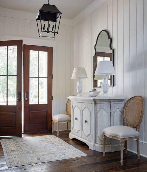 The elegance of this Beach -style foyer comes from the dark hardwood flooring paired with a dresser cabinet bearing a couple of table lamps flanking a wall-mounted mirror. This is given a homey background of a daylight-bathed white shiplap walls.