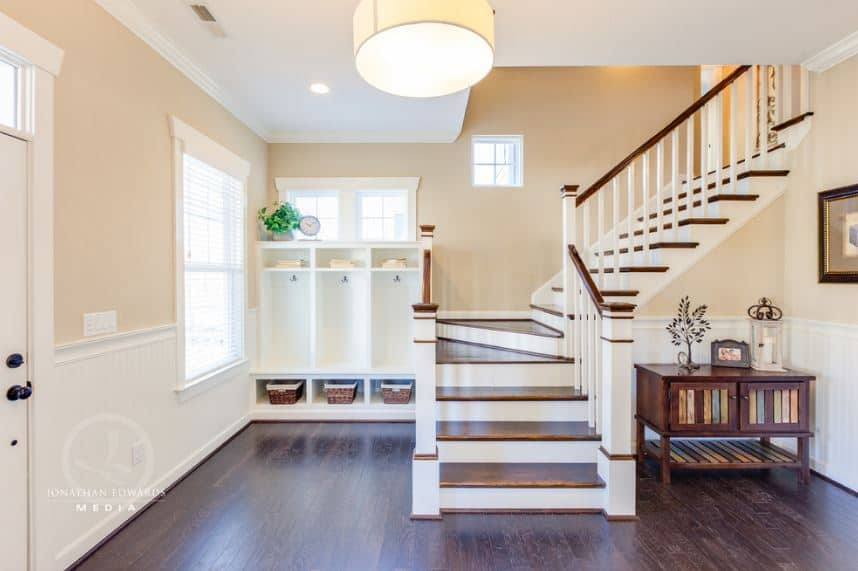 The delightful yellow walls of this Beach-style foyer are brightened by the white wainscoting that blends with the white mudroom on the side of the stairs with steps the same as the dark wooden flooring that stands out against the brightness.
