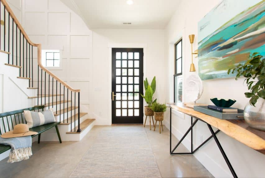 The dark wooden main door is adorned with small glass panels arranged in a checkered pattern. This brings in an abundance of natural light on the white walls adorned with potted plants by the door and a wooden console table on the side.