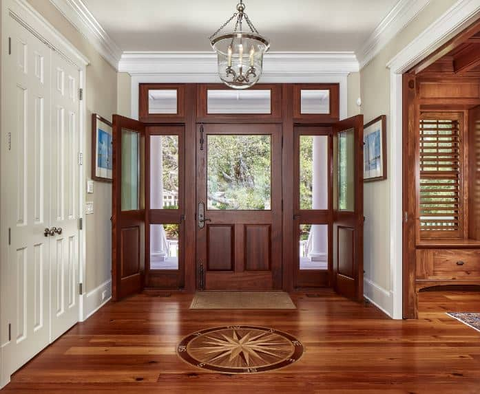 This simple Beach-style foyer has wooden main door with a large glass panel that matches the side lights and transom windows all casting natural lights on the hardwood flooring adorned with a seafaring compass topped with a pendant light hanging from the white ceiling.
