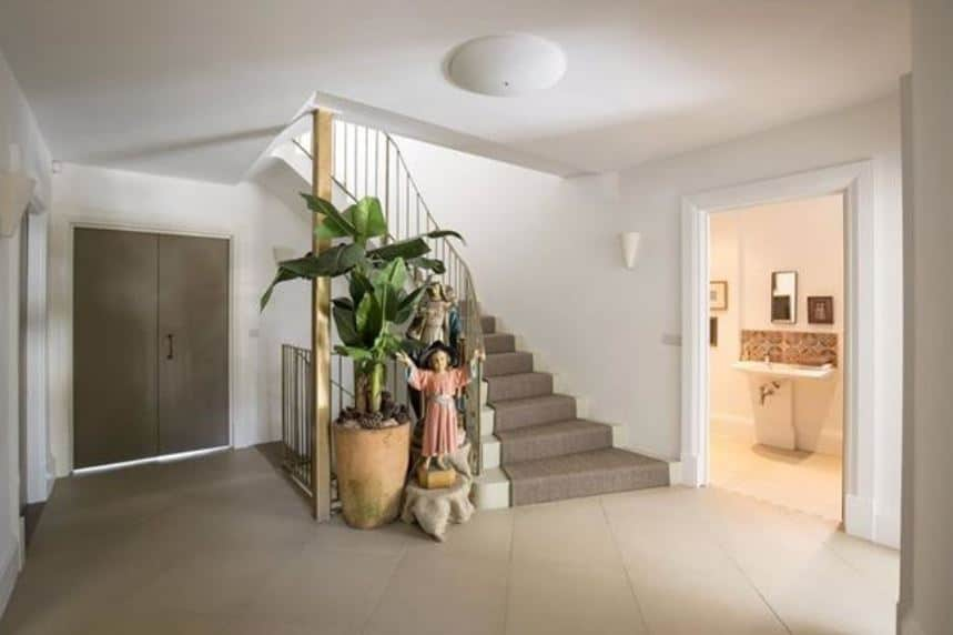 The simplicity of this Beach-style foyer is augmented with some Spanish religious flair brought by the statuettes beside a large potted plant that brings in a bit of color for the beige flooring and white walls contrasting the dark gray main doors.