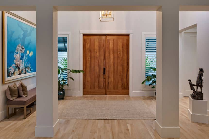 This is a wide Beach-style foyer through double doors made of wood that complements the light hardwood flooring topped with a rustic woven area rug. This foyer is elevated by the artworks like the large painting and sculpture on the side.