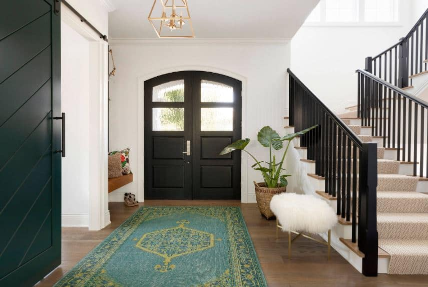 The green patterned area rug covering the hardwood flooring matches with the potted plant on bringing a green color to the Beach-style foyer that is mostly black and white adorned with sitting areas by the door and by the stairs.