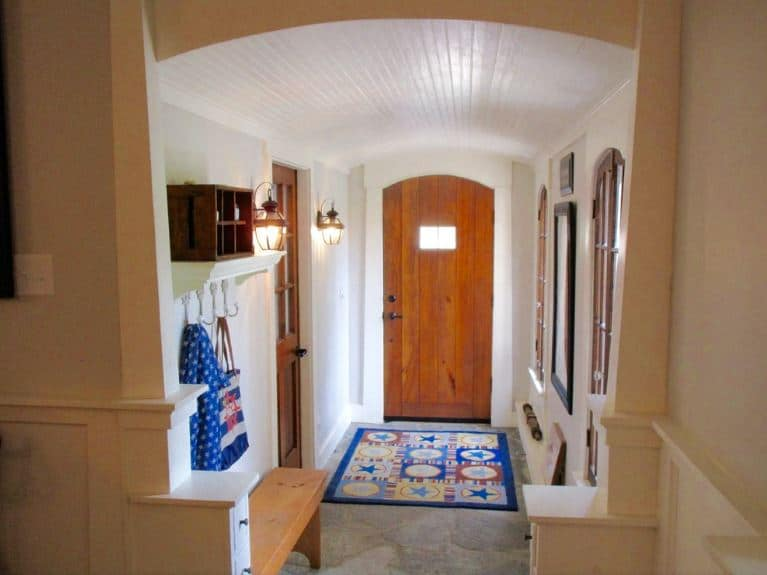 This is a delightful and homey Beach-style foyer that gives its guests a snug and intimate welcome with a dash of color from the area rug and a mudroom on the side of the white wall with a wooden bench and wall-mounted lamps.