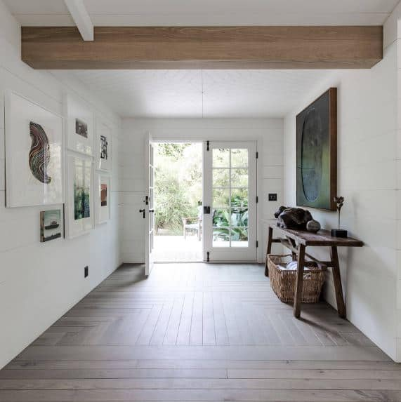 A whole lot of natural lighting enters through the double doors that are filled with glass panels. This makes the hardwood flooring lighter and the white walls brighter complemented by the framed artworks and the rustic elements.