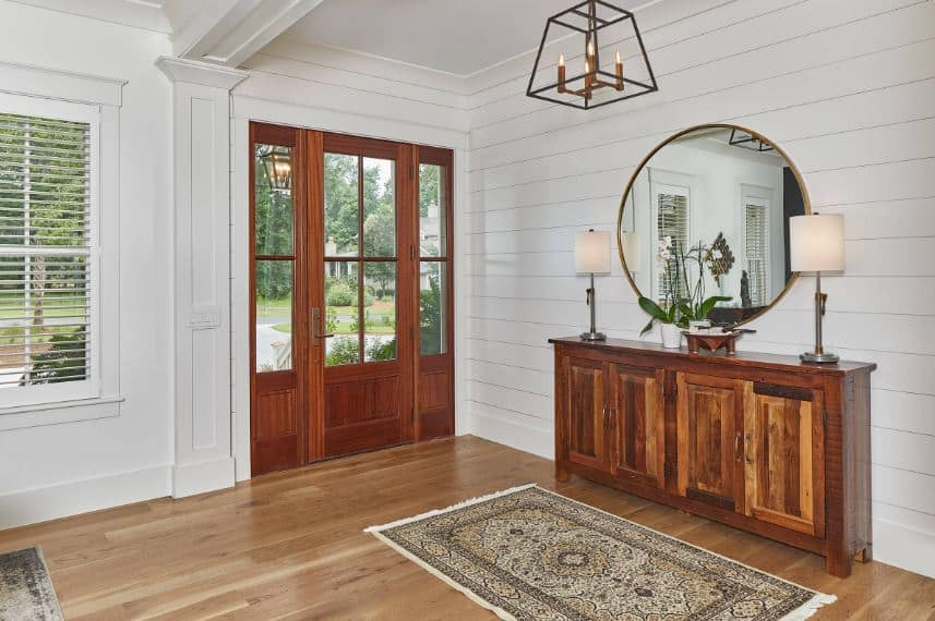 Upon entry of the wooden door with side lights, guests are welcomed by a wooden console table with cabinets bearing modern table lamps flanking a circular mirror mounted on the white shiplap walls that contrast the hardwood flooring.