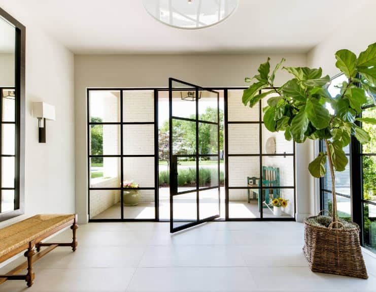 This bright Beach-style foyer doubles its welcome with an outdoor and indoor patio separated by a glass wall with a swiveling glass door with black frames that stand out against the white flooring adorned with a potted plant and a wooden bench.