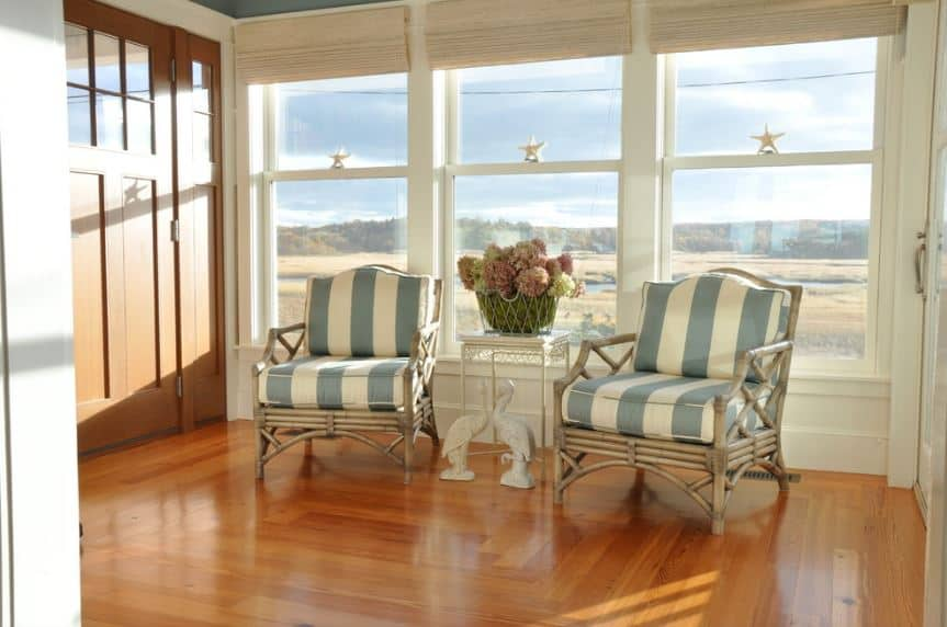 This bright Beach-style foyer is bathed in natural light from the row of tall windows adjacent to the wooden main door. It has a sitting area with two bamboo armchairs that have blue-striped cushions that go well with the hardwood flooring.