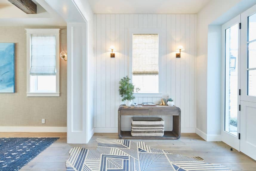 The light hardwood flooring of this foyer is topped with a blue patterned area rug that offers a dash of color to the white shiplap walls softened by warm yellow lights of the wall-mounted lamps flanking the window above the wooden table.