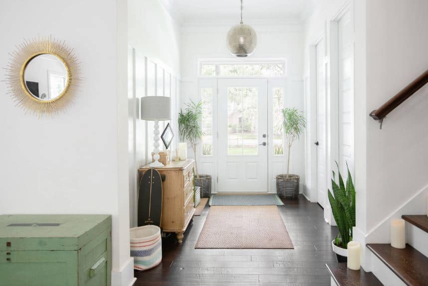 The brilliant white main door has a glass panel on it that matches the side lights in bringing in natural lights enjoyed by the two potted plants on the corners. There is a dresser on the side that matches the area rug over the dark hardwood flooring.