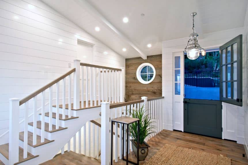 The two-part farmhouse-style main door has a dark gray hue that stands out against the white side lights that blend into the white shiplap walls and white shed ceiling that hangs a pendant light over the hardwood flooring topped with a rustic area rug.