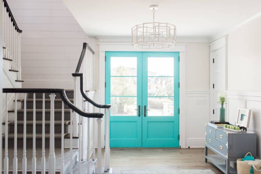 The light green double doors stand out against the white walls and ceiling that has a white modern chandelier. The light gray console table on the side that has drawers and decors are a good complement to the hardwood flooring leading to a staircase with black and white railings.