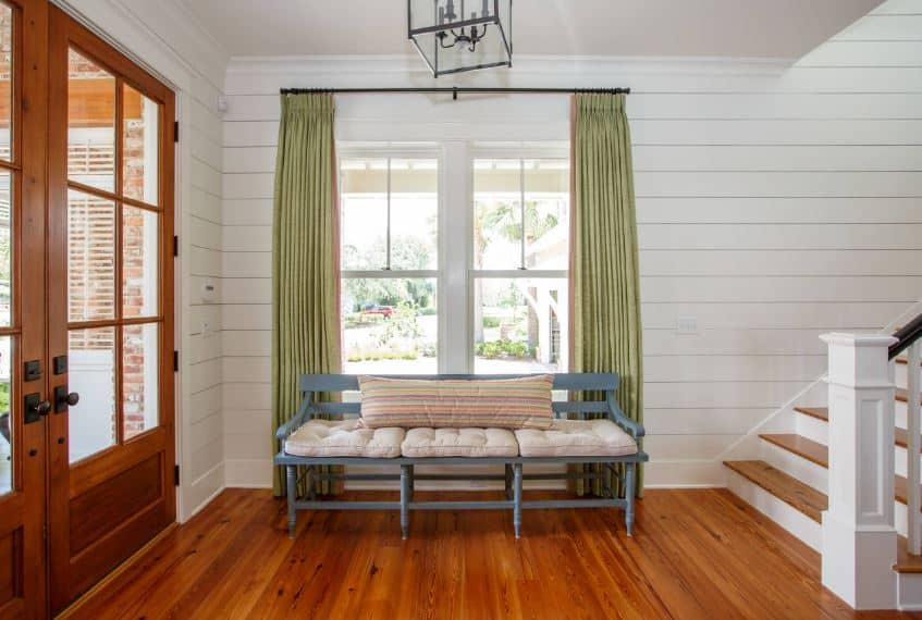 This Lovely Beach-style foyer has redwood flooring that matches with the wooden double doors with glass panels. These contrasts the white shiplap walls with a green curtained window above the wooden gray bench on the side.