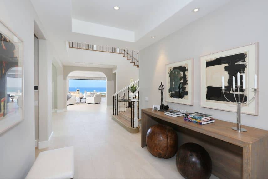 The bright and white tray ceiling and flooring of this Beach-style foyer matches the white walls that are accented with framed artworks and a wooden console table bearing decors on it and a couple of wooden spherical chairs underneath.