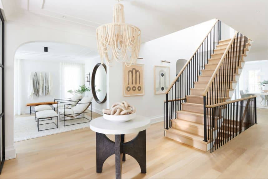 The beige hood of the chandelier hanging from the white tray ceiling matches the decors on the round wooden table. This also matches the light hardwood flooring and the steps of the staircase that has black iron railings.