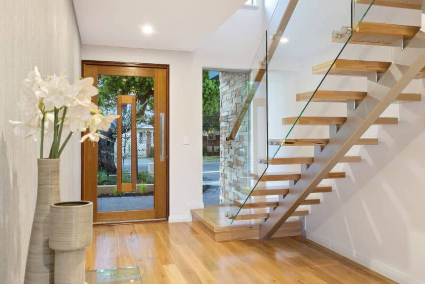 The beautiful glass main door has a wooden frame that stands out against the white walls and matches the hardwood flooring as well as the steps of the staircase with glass on the side matching the large window beside the door.