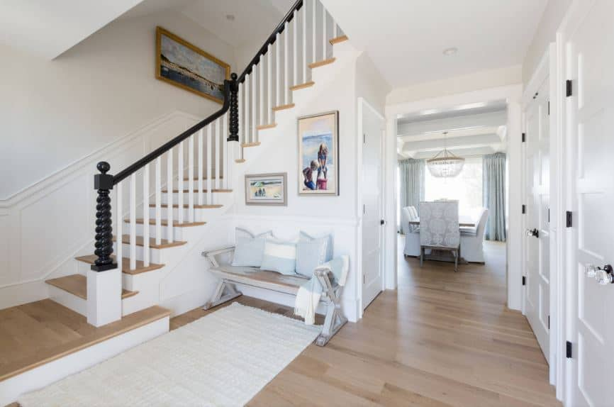 There is a lovely sitting area for the guests of this Beach-style foyer by the stairs that has wooden steps the same as the light hardwood flooring that is topped with a white area rug matching the walls adorned with framed photos.