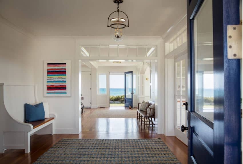 Through the wooden blue door of this Beach-style foyer, the guests will see a similar blue door on the other end of the house that opens to the seaside scenery outside. There is a nice sitting area with a white wooden bench that goes well with the white walls.