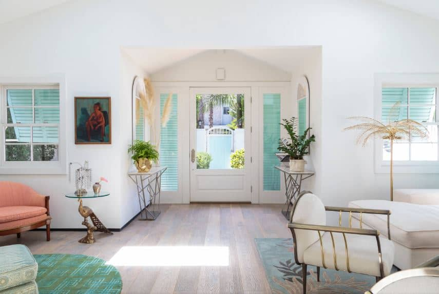 The white wooden main door has a large glass panel on it that matches with the side lights and the arched windows on the adjacent walls of the foyer. These are given a green hue due to the shutters outside matching the various green elements of the interiors.
