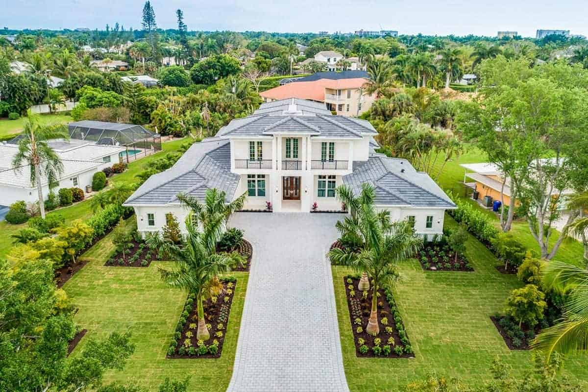 This house has a large front yard with a wide light gray stone walkway and driveway that is flanked with two large grassy lawns that showcases symmetry in its shrubs and tropical trees showing a lovely tamed version of nature.