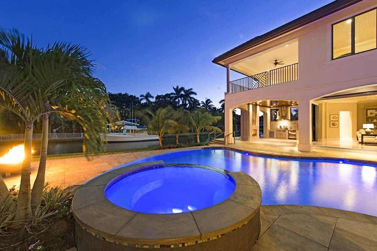 The beautiful pool has lighting in it that makes it glow blue that stands out against the gray stone flooring of the backyard that is accented with warm yellow lights as well as a few sprouting tropical trees that completes the aesthetic.