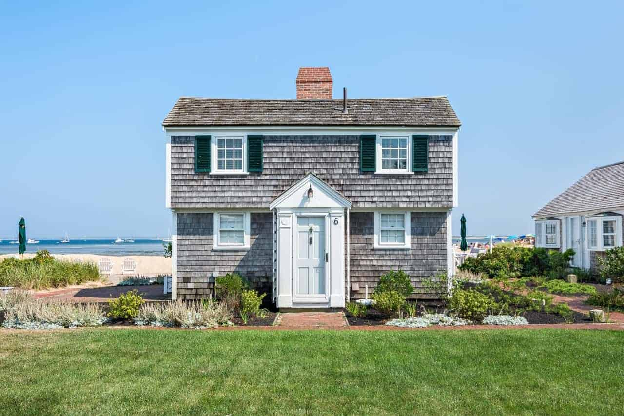 The tiny detached house with gray wooden exterior is provided with a large and expansive Beach-style landscaping that prioritizes the view of the sea behind the house with only low-growing shrubs and a well-manicured lawn of grass.