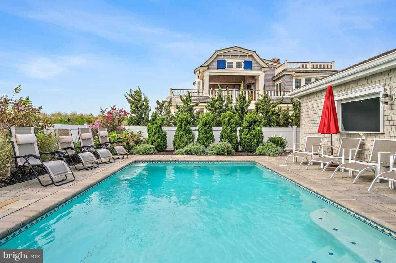 The backyard of this house showcases the blue pool that has brilliant blue tiles on its sides that contrast the gray stone flooring adorned with various lawn chairs that has a background of shrubberies and flowers.