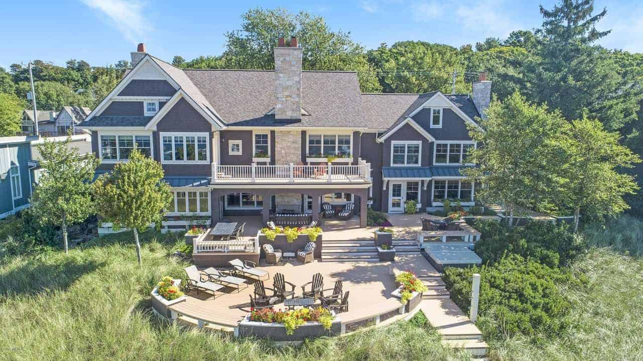 This backyard view of the house from above features a large area filled with grass and tall trees on either side of the large patio with outdoor dining areas and various relaxing sitting areas while enjoying the lovely landscape.