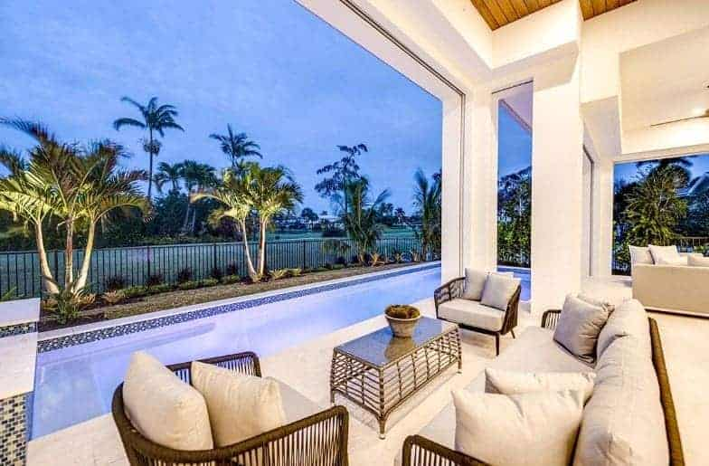 This backyard view of the house has a charming patio with comfortable couches and armchairs you can relax on while enjoying the view of a pool with colorful tiles that complement the landscaping of tropical trees and shrubs outlining the pool.
