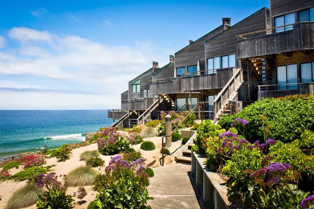 This charming wooden house has a wooden staircase leading down to the seaside lot of land that is adorned with various colorful flowering shrubs that go well with the sandy beach.