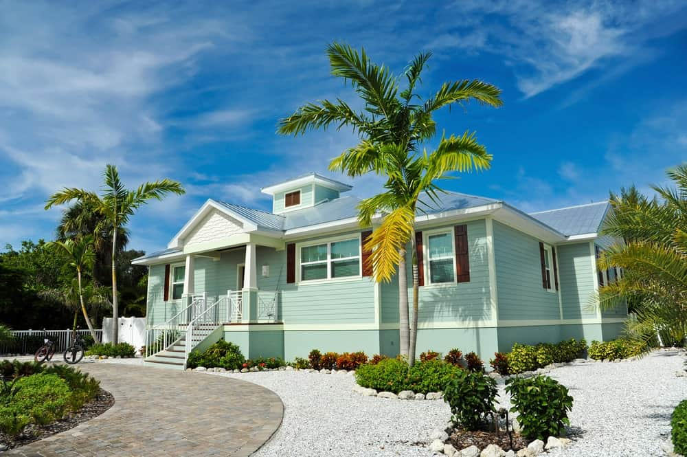 The light green exteriors of the house has a cheerful quality to it that is accented with various colorful shrubs and tropical trees that frame the charming home with a lush landscape that is fresh and relaxing to look at.