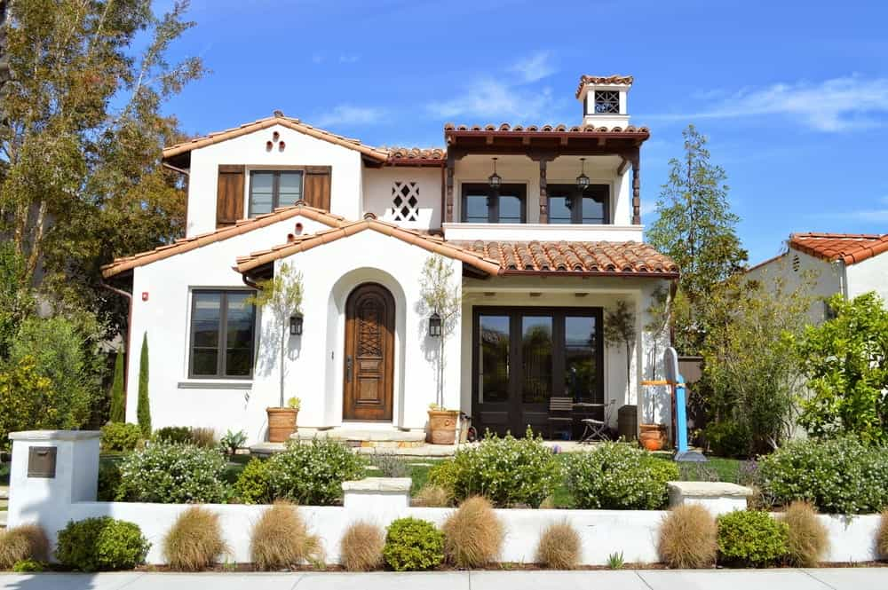 The earthy clay roofing of this charming home matches with the clay pots of the plants flanking the arched entryway with a wooden arched door that has elegant carvings on it. This is given a lovely foreground of various shrubs and a low white fence.