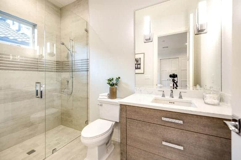 The modern wooden vanity has stainless steel handles that matches with the fixtures of the white sink and the shower area that has beige marble tiles on its flooring and walls adorned with a narrow window.