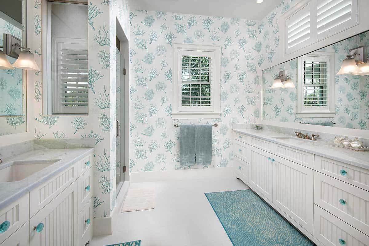 The lovely wallpaper that dominates the walls of this Beach-style primary bathroom is filled with green tree patterns against the white background. This aesthetic is mirrored on the white wooden vanities with green crystal handles as well as on the green patterned area rug over the white flooring.