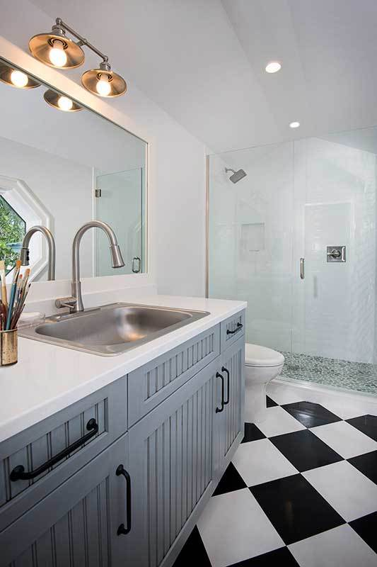 This simplicity of this bathroom is elevated by the black and white checkered flooring that goes well with the light gray wooden vanity with black handles contrasting the white countertop with a mirror adorned with an industrial wall lamp.