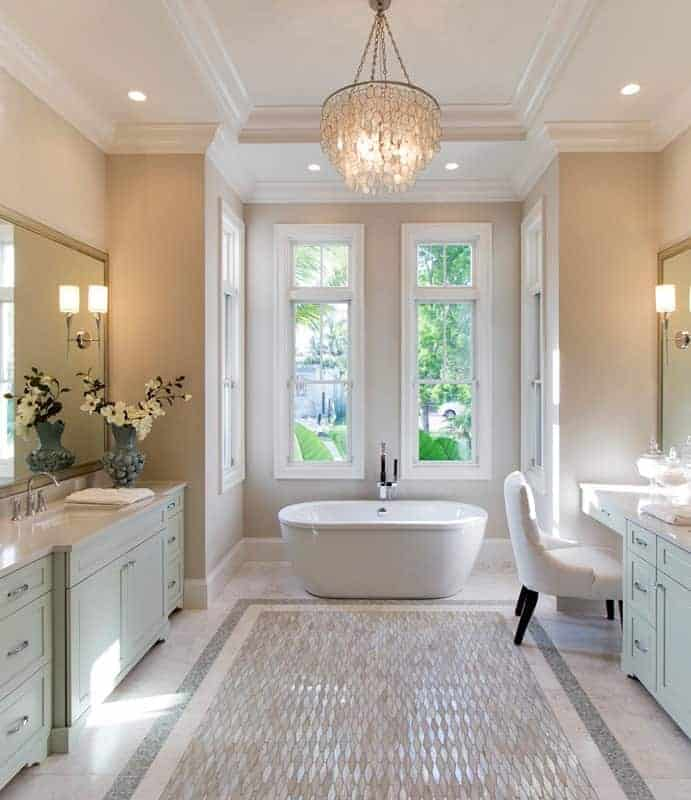 The beige marble flooring of this elegant Beach-style bathroom has a patterned middle area that matches well with the pendant light hanging from the white tray ceiling complemented by beige walls and white windows surrounding the freestanding bathtub at the far wall in an alcove.