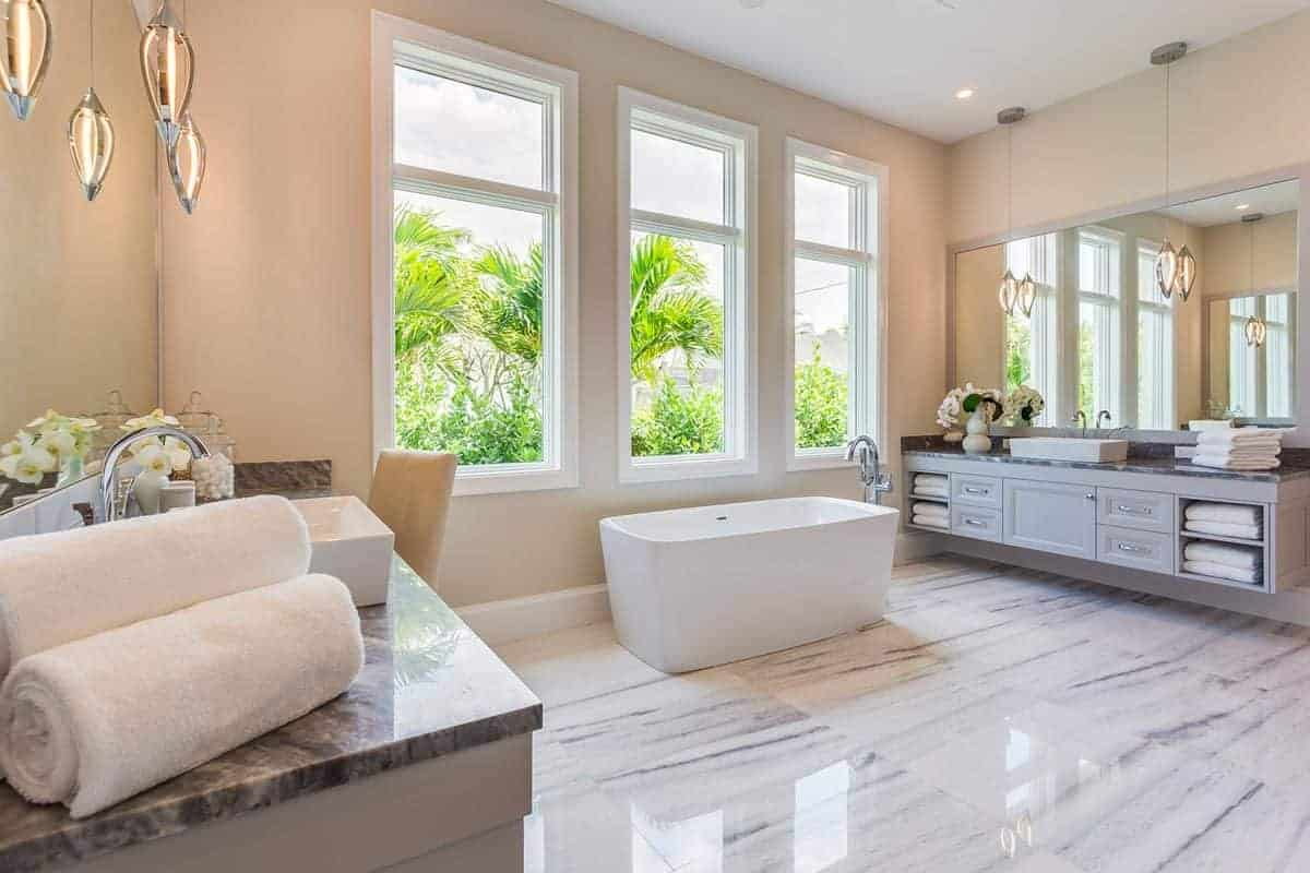 The white marble flooring of this spacious bathroom is illuminated by the tall white windows above the freestanding white bathtub in the middle of two floating light gray vanities with drawers and shelves and adorned with teardrop pendant lights.