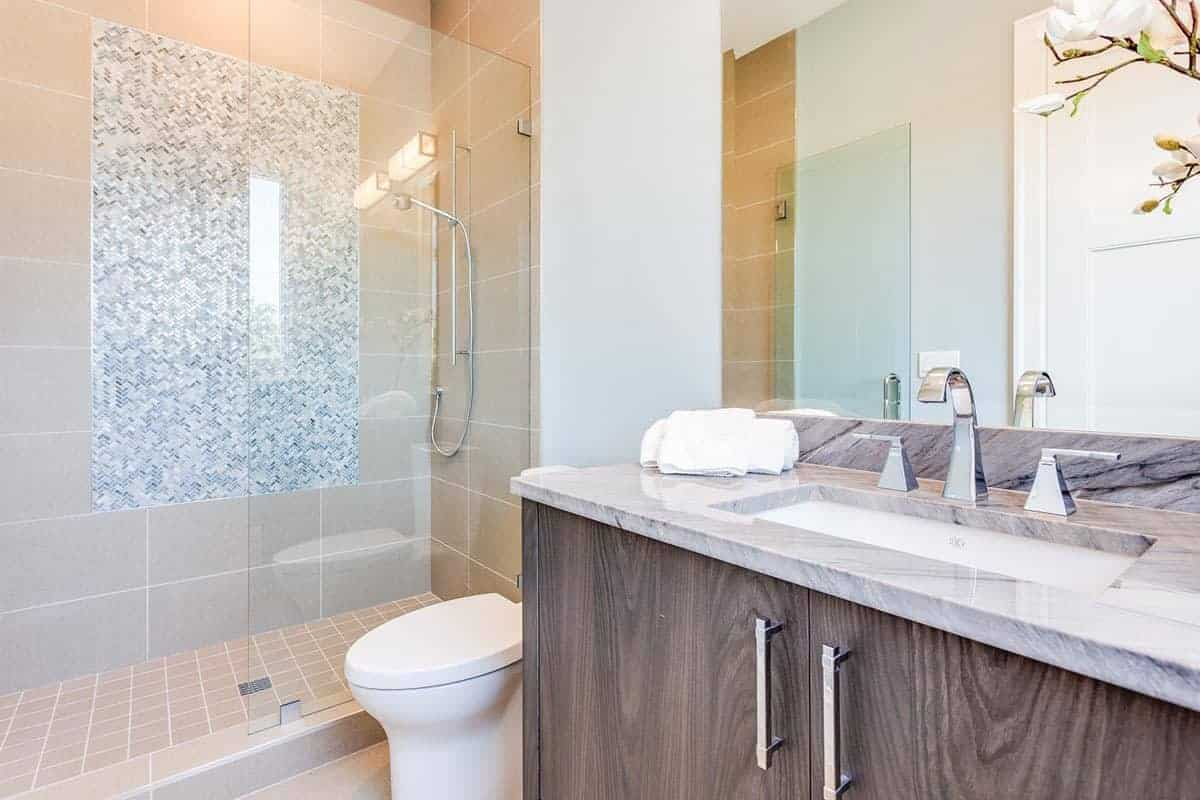 The brightness of this simple Beach-style bathroom lightens up the beige tiles of the shower room that is separated from the rest of the bathroom with a glass wall matching the mirror above the wooden vanity with a white marble countertop paired with a modern faucet.