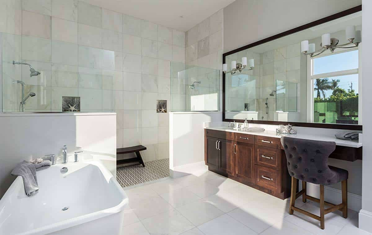 This Beach-style bathroom is large enough for two shower area on the far wall across each other behind half-glass walls. One is beside the white freestanding bathtub while the other is beside the wooden vanity that stands out against the white flooring tiles.